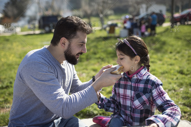 Father feeds girl a sandwich