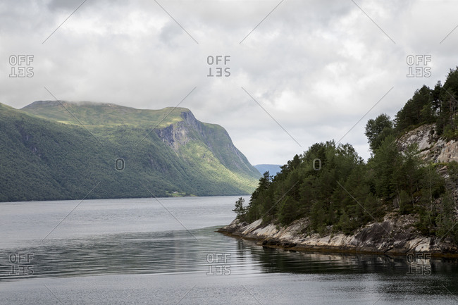 Norwegian fjord landscape under cloudy sky