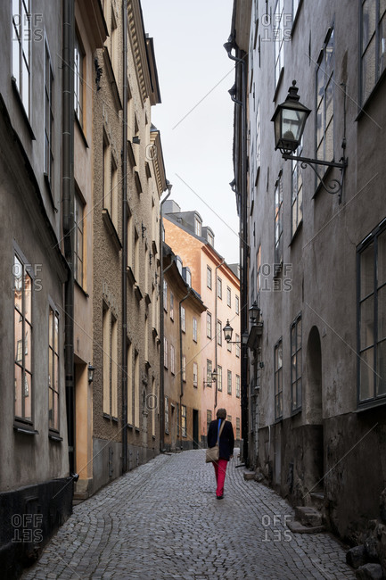 Rear view of person walking down alleyway in downtown Stockholm, Sweden