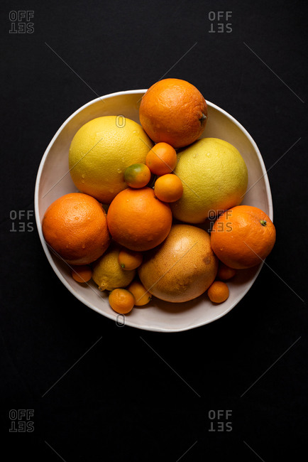 Top down of bowl of citrus fruit on a dark background