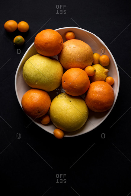 Top down of bowl of citrus fruit in a bowl on a dark background