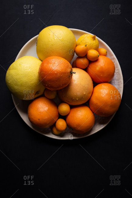 Top down of plate of citrus fruit on a dark background