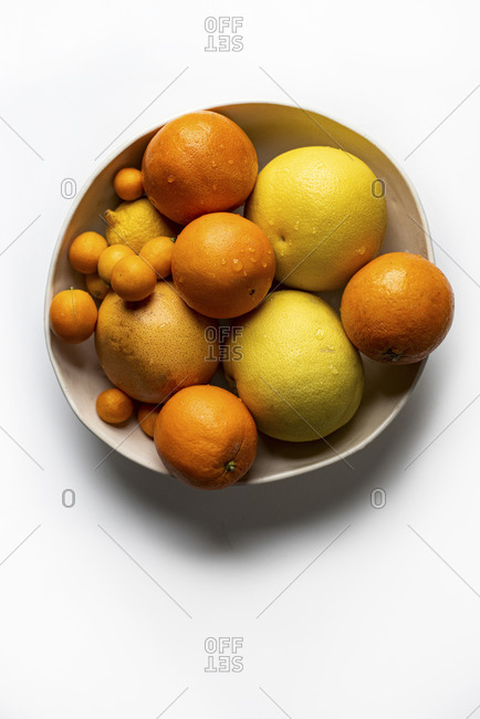 Top down of bowl of citrus fruit on a light background