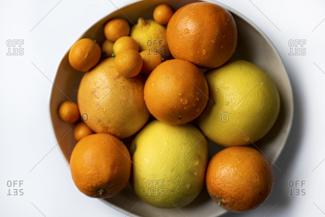 Overhead view of bowl of citrus fruit on a light background