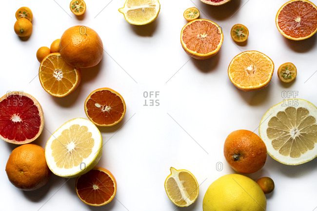 Various sliced citrus fruits on a light background