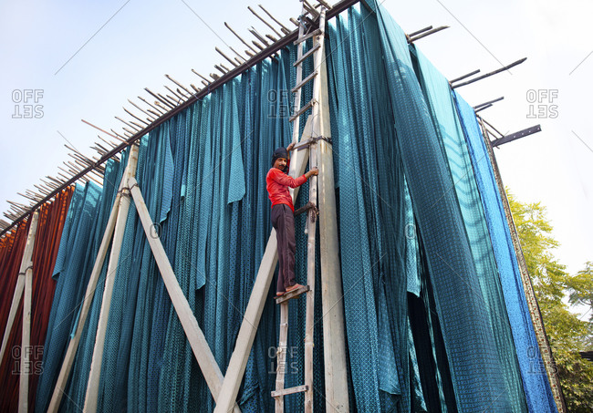 Jaipur, India - January 2, 2020: Low angle view of textile dying worker on ladder