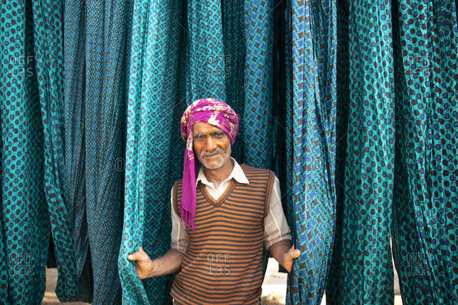 Jaipur, India - January 2, 2020: Textile dying worker standing among blue patterned cloth