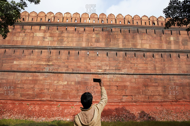 Indian tourist taking photograph of red fort with smart phone, New Delhi, India