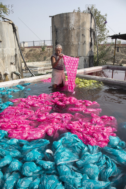 Jaipur, India - January 2, 2020: Textile dying worker in a vat of water with dyed cloths