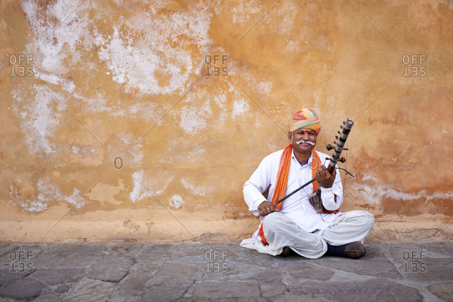 Man playing music for tourists and coins outside entrance way at the Amber Fort, Jaipur, India