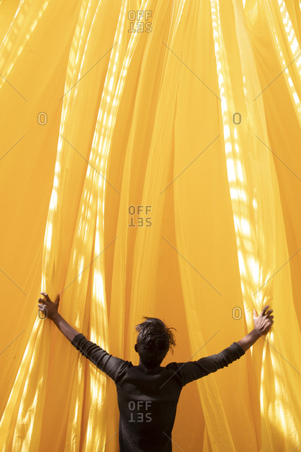 Rear view of a textile dying worker inspecting yellow dyed fabric