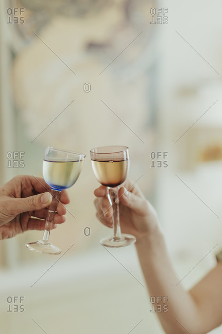 Close up of couple clinking small wine glasses together for toast