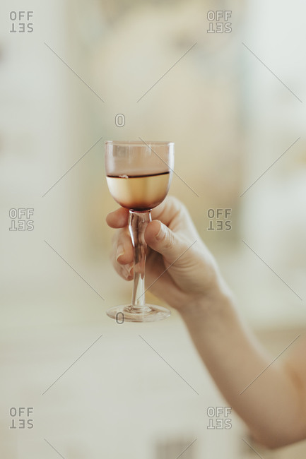 Woman holding a small wine glass up for a toast