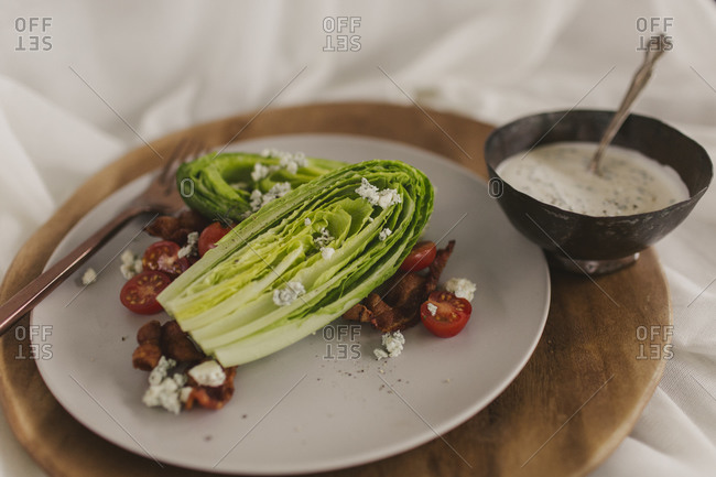 Romain lettuce wedge salad with blue cheese, tomato and bacon with dressing on side