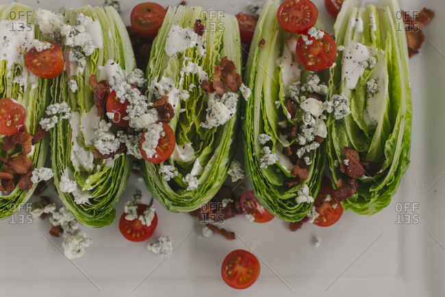 Romain lettuce salad wedges with blue cheese, tomato and bacon