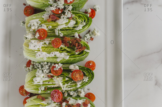 Romain lettuce salad wedges with blue cheese, tomato and bacon on white marble counter