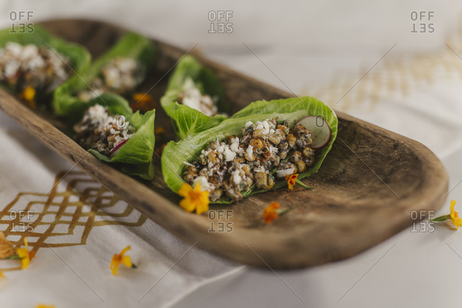 Close up of lettuce wraps on a board on white marble surface