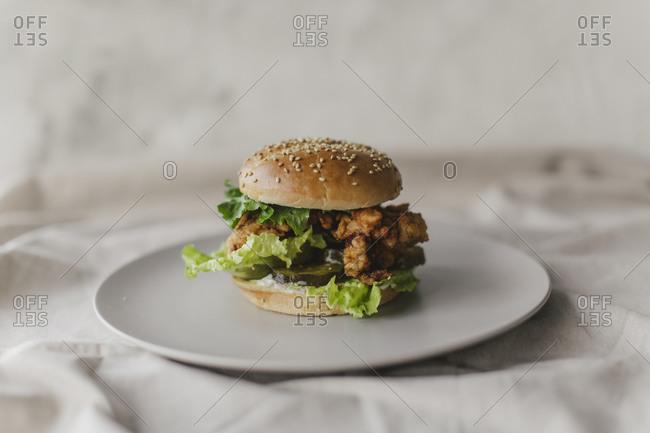 Fried chicken sandwich on a plate on light background