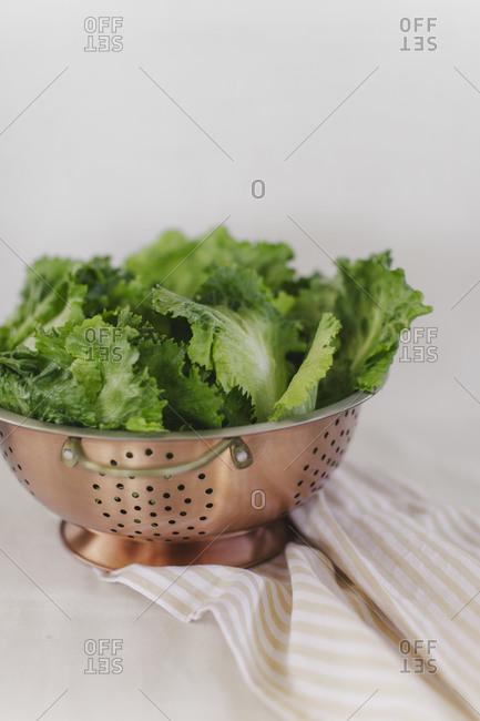 Lettuce leaves in a copper colander