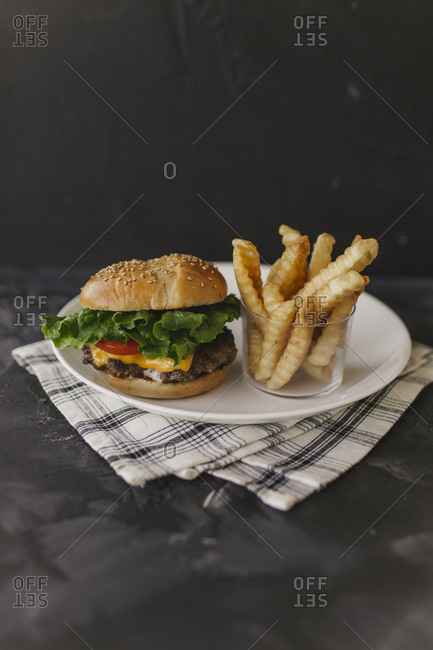Cheeseburgers with fries on dark background