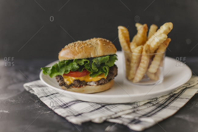 Cheeseburgers with French fries on dark background