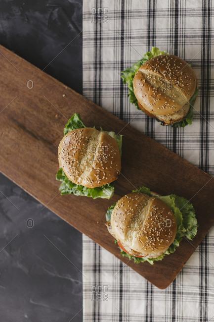 Overhead view of grilled chicken sandwich on dark background