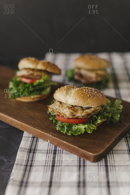 Grilled chicken sandwiches on a wooden board
