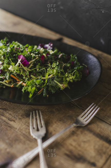 Close up of a leafy salad on a rustic wooden table