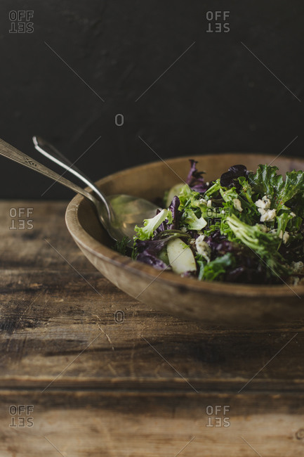 Close up of a leafy salad in a wooden bowl on a rustic table