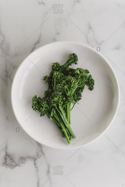 Broccolini on a white plate on marble surface