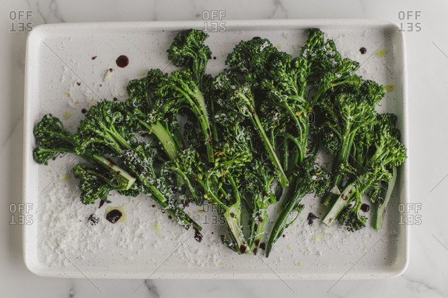 Overhead view of broccolini on a white plate on marble surface