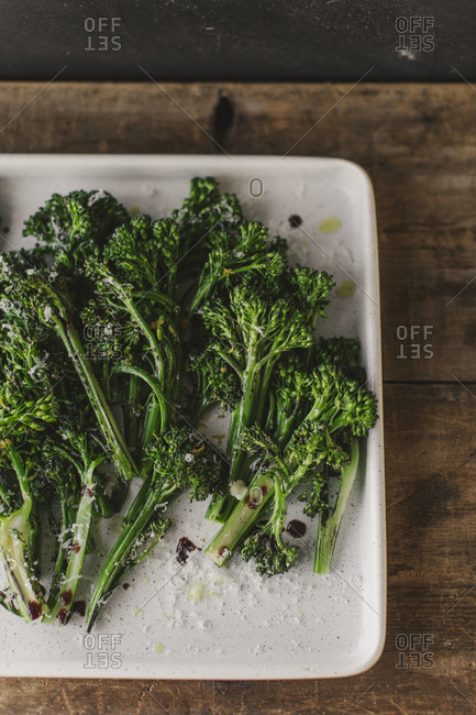 Overhead view of broccolini on a white plate on rustic table