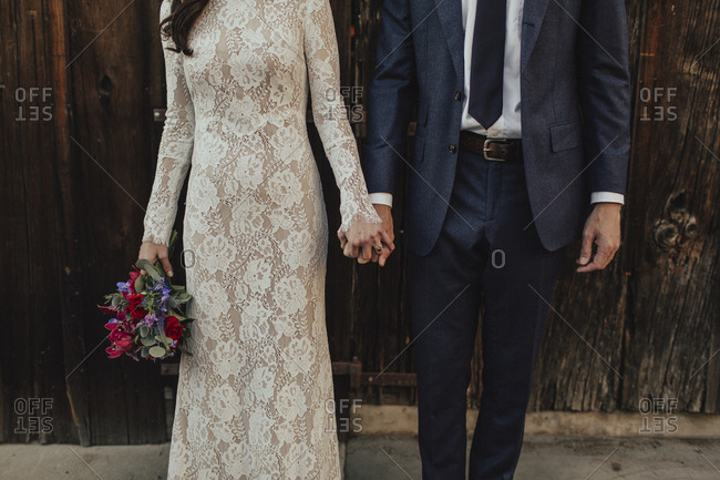 Mid-section of bride and groom holding hands