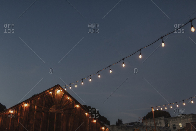 Illuminated strand lights hanging from rustic building