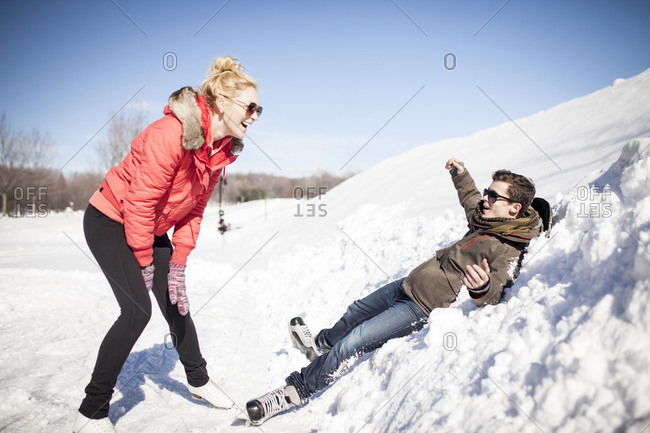 Attractive couple play fighting while ice skating outdoors
