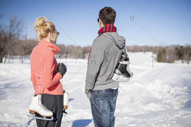 Young fashionable couple standing together holding ice skates