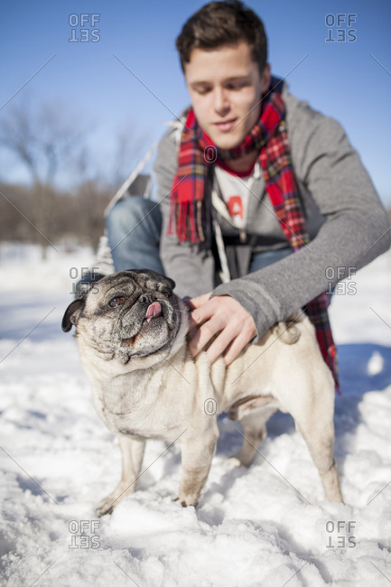Man with little dog outdoors in snow