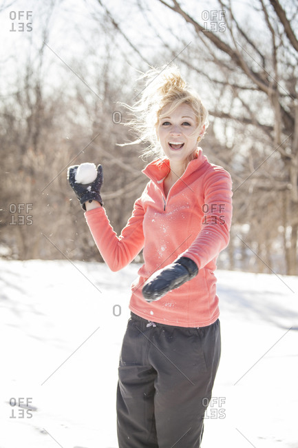 Beautiful young woman throwing snowball in the forest