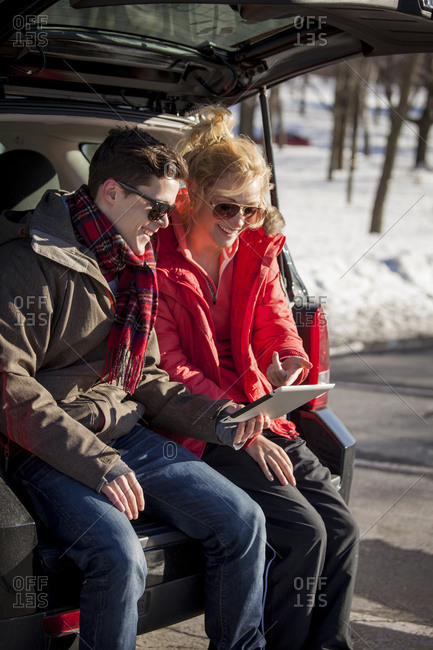 Young couple sitting in the back of a truck on tablet parked in parking lot