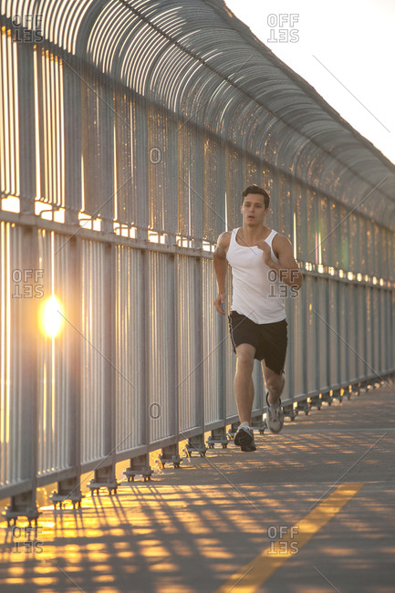 Young man running on bike path in urban city setting at sunset
