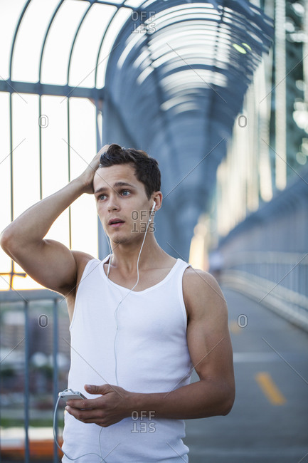 Young man resting after running while listening to music in urban city setting at sunset