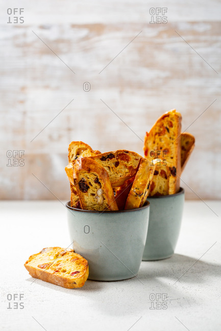 Sliced homemade biscotti in two cups against white wooden wall