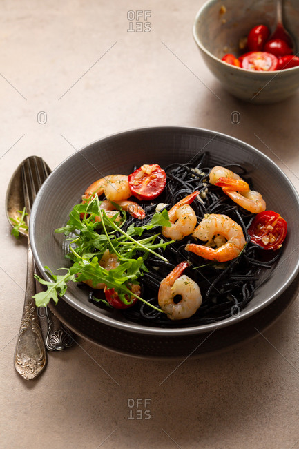 Black pasta with roasted shrimps in bowl
