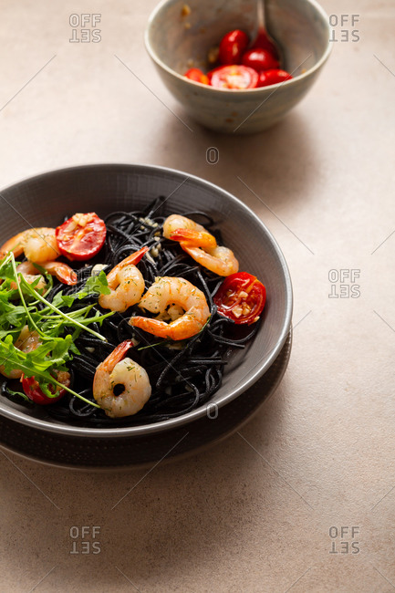 Black pasta with roasted shrimps in bowl on light surface