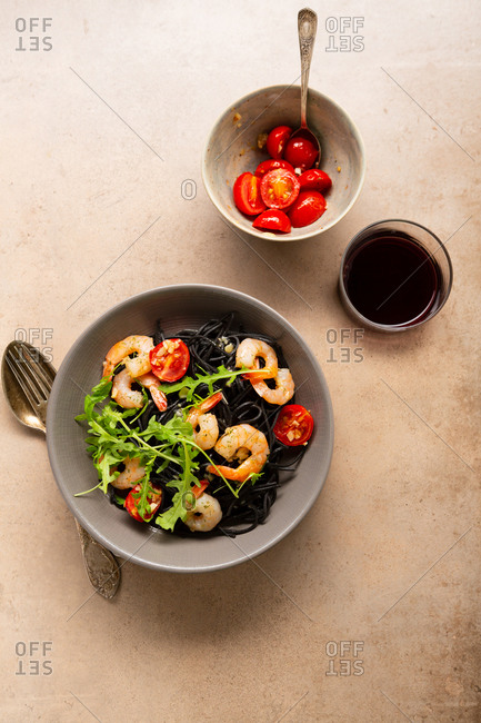 Overhead view of black pasta with roasted shrimps in bowl on light surface