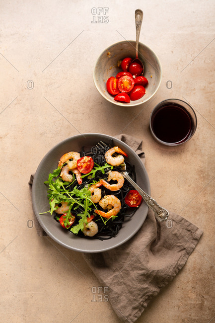 Overhead view of black pasta and wine on light surface