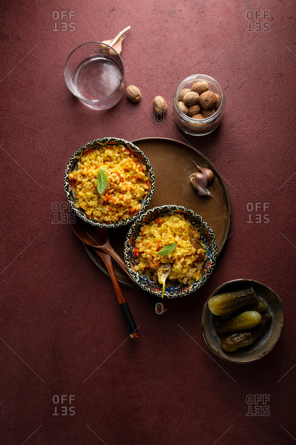 Overhead view of curry rice in two bowls on dark red background