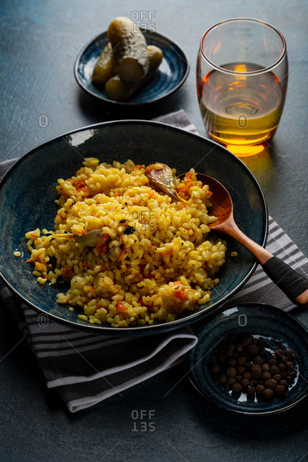 Pilaf in blue bowl and wooden spoon