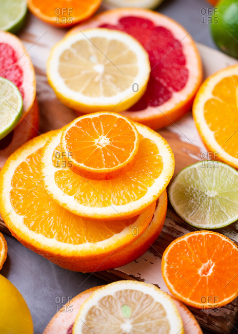 Various sliced citrus fruits on wooden cutting board