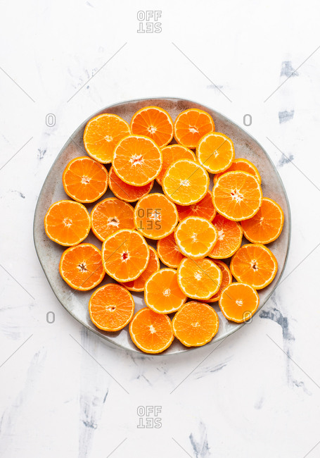 Overhead view of big ceramic plate with sliced tangerines